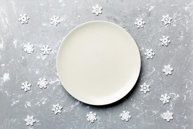 Draufsicht der leeren platte umgeben mit schneeflocken