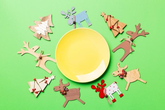 Draufsicht der leeren platte und der dekorationen des neuen jahres auf buntem, umhüllung des neuen jahres für festliches abendessen, ren und weihnachtsbaum, feiertagsfamilien-abendessenkonzept,