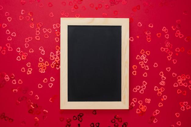 Draufsicht der leeren tafel auf rotem hintergrund mit glänzendem confett.