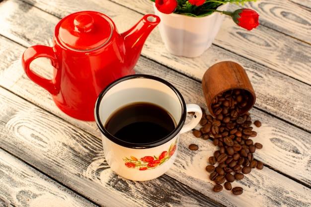 Draufsicht der leeren tasse mit den braunen kaffeesamen und blumen des roten kessels auf dem hölzernen schreibtisch