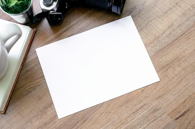 Draufsicht der leeren weißen karte mit alter kamera und buch auf holztisch.