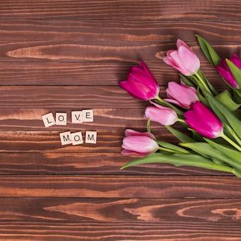 Draufsicht der liebe; mama; text mit rosa tulpenblumen auf hölzernem schreibtisch