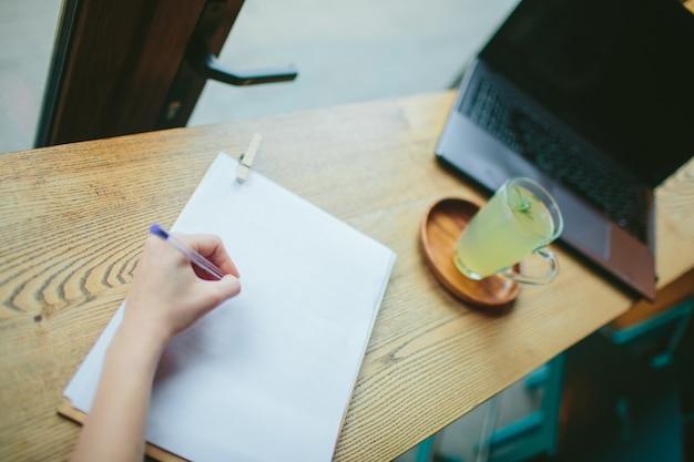 Draufsicht der linken hand der frau, die etwas auf weißem papier schreibt. mädchen sitzt am schreibtisch im café. verschwommenes bild des holztischs mit laptop-computer und zitronengetränk. studentin oder geschäftsfrau