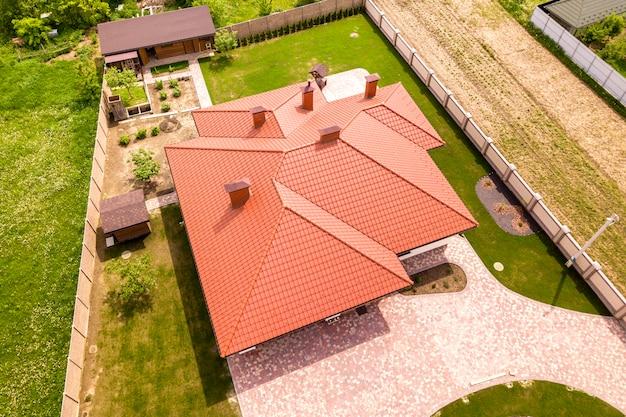 Draufsicht der luft des neuen wohnhaushäuschens mit schindeldach auf eingezäuntem großem yard am sonnigen tag.