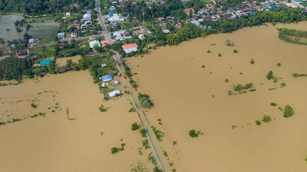 Draufsicht der luft von überschwemmten reisfeldern und von dorf, ansicht von oben schoss durch brummen