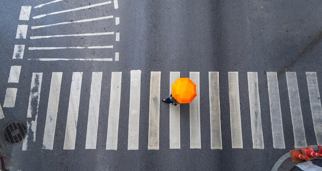Draufsicht der luftfoto von leuten gehen auf straße in der stadt über fußgängerüberwegverkehrsstraße