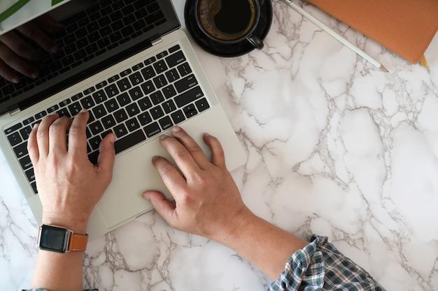 Draufsicht der männlichen arbeitskraft schreibend auf laptop auf marmorschreibtisch
