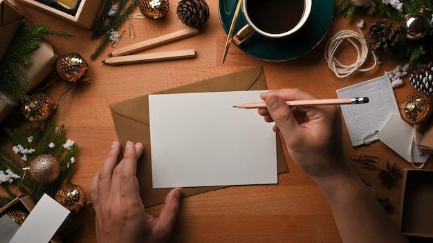 Draufsicht der männlichen hände, die grußkarte auf holztisch schreiben, der mit weihnachtsdekorationen verziert ist