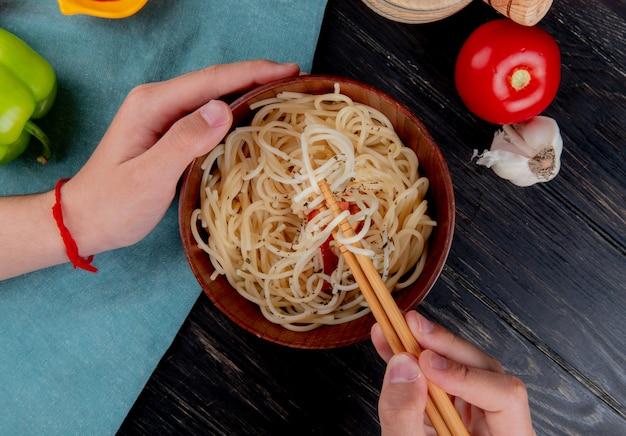 Draufsicht der männlichen hände, die stäbchen und schüssel mit makkaroni-nudeln mit tomaten-pfeffer-knoblauch auf holzoberfläche halten