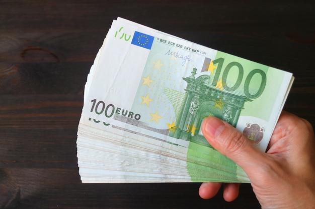 Draufsicht der männlichen hand bündel von hundert eurobanknoten auf dunkelbraunem holztisch halten
