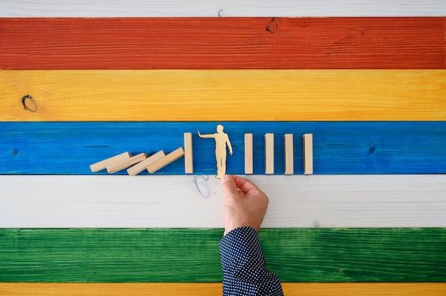 Draufsicht der männlichen hand, die papierschnittschattenbild eines mannes platziert, um einzugreifen und zu verhindern, dass dominosteine zusammenbrechen.