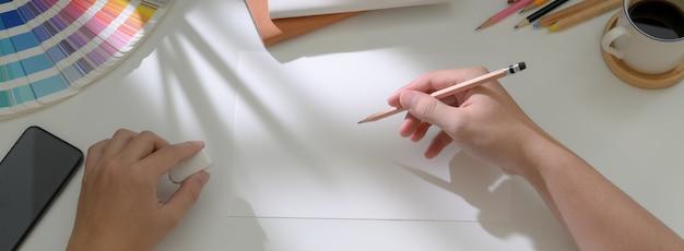 Draufsicht der männlichen künstlerzeichnung auf skizzenpapier auf weißem arbeitstisch