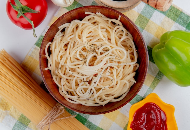 Draufsicht der makkaroni-nudeln in der schüssel mit tomaten-schwarzem pfeffer-ketchup-knoblauch-pfeffer und fadennudeln auf kariertem stoff und weiß