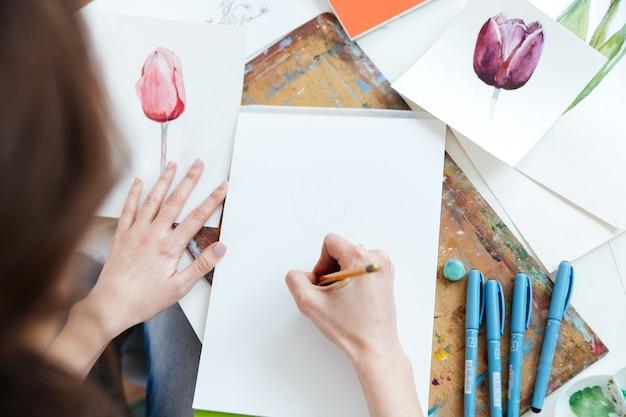 Draufsicht der malerin, die am tisch sitzt und mit bleistift zeichnet