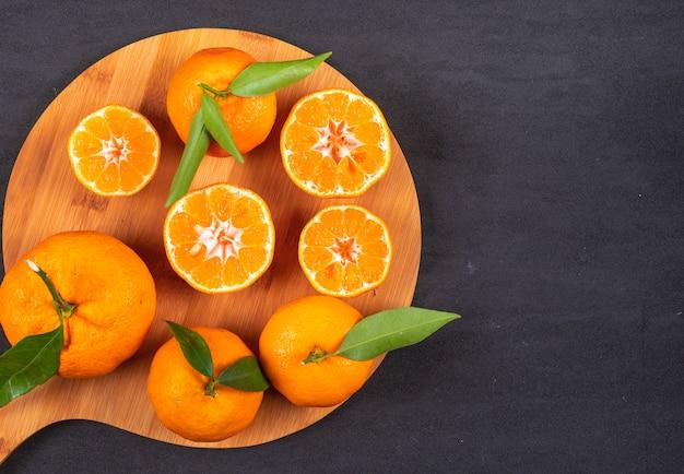 Draufsicht der mandarinen über hölzernes schneidebrett auf schwarzer steinoberfläche