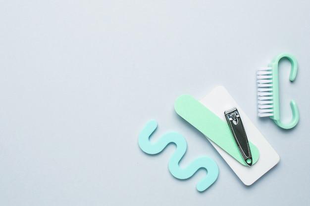Draufsicht der maniküre- und pediküreausrüstung auf blauem hintergrund mit raum für ihren text