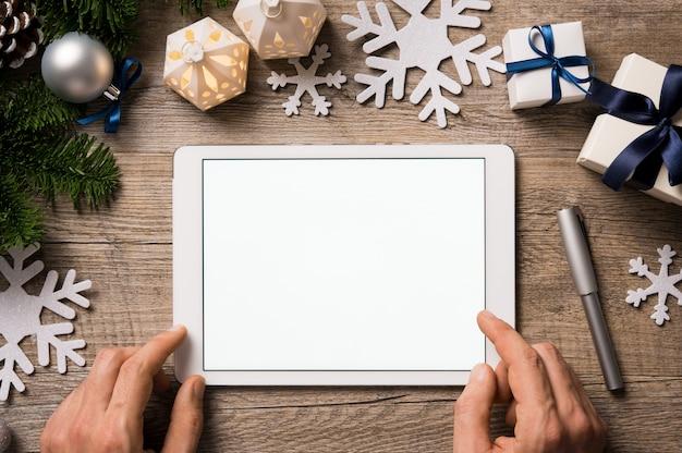 Draufsicht der mannhände unter verwendung der digitalen tablette auf holztisch mit weihnachtsverzierungen.