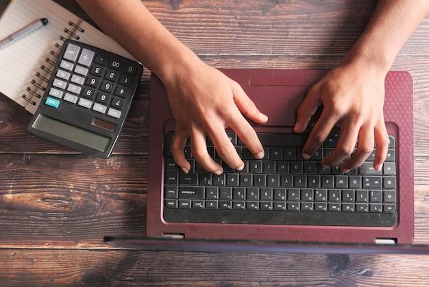 Draufsicht der mannhand, die auf laptop tippt.