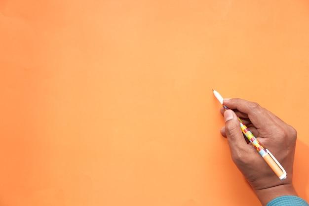 Draufsicht der mannhand, die auf orange papier schreibt.