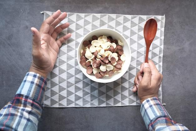 Draufsicht der mannhand, die cornflakes isst