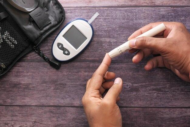 Draufsicht der mannhand, die diabetiker auf tisch misst
