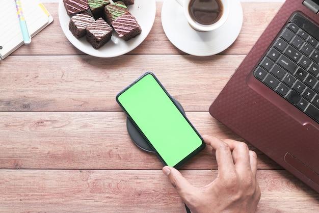 Draufsicht der mannhand unter verwendung des smartphones am schreibtisch