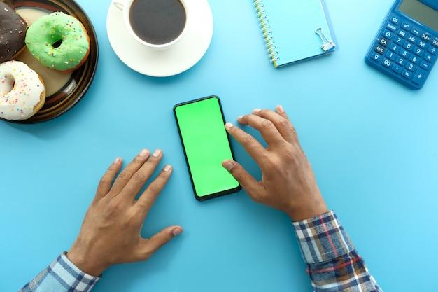 Draufsicht der mannhand unter verwendung des smartphones mit donuts, tee blaue oberfläche