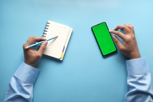 Draufsicht der mannhand unter verwendung des smartphones und des schreibens auf notizblock