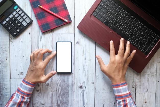 Draufsicht der mannhand unter verwendung des smartphones und des tippens auf laptop.