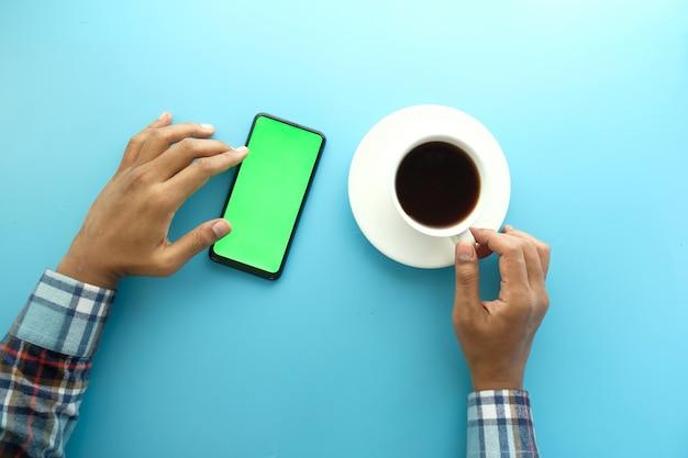 Draufsicht der mannhand unter verwendung des smartphones und des trinkens von tee