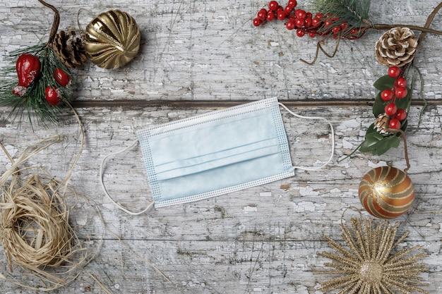 Draufsicht der maske mit weihnachtsdekoration auf strukturiertem hintergrund