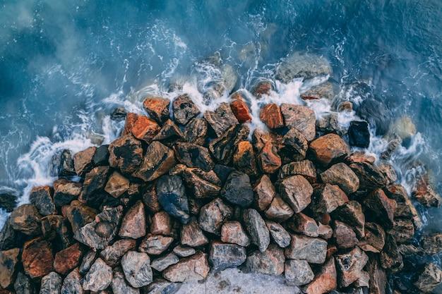 Draufsicht der meereswellen, die auf küstensteinen brechen