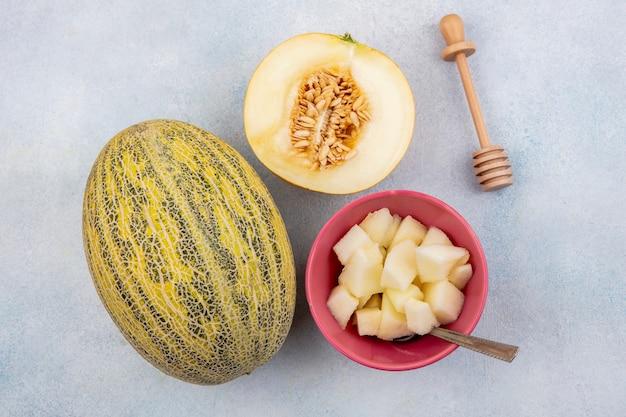 Draufsicht der melone melone mit melonenscheiben auf rosa schüssel mit honiglöffel auf weiß
