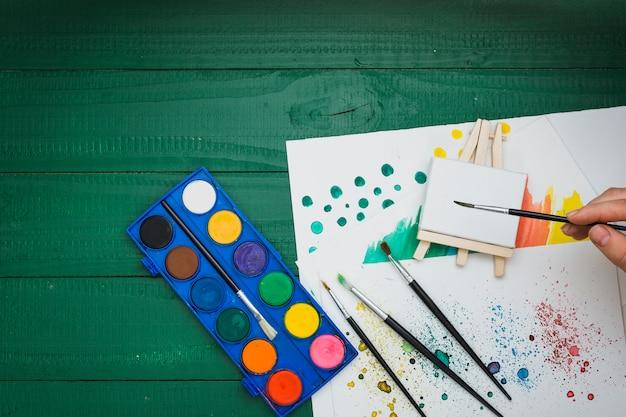 Draufsicht der menschlichen hand malerpinsel über malender ausrüstung halten