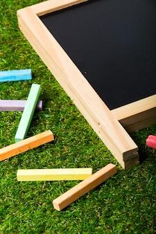 Draufsicht der minitafel und der farben auf plastikgras. konzept zurück in die schule
