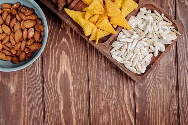 Draufsicht der mischung aus salzigen biersnacks, sonnenblumenkernen, maiskegeln und mandeln auf rustikalem holz mit kopierraum