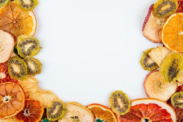 Draufsicht der mischung von getrockneten früchten und zitrusfrüchten apfelorangen-kiwi und ananasscheiben auf weißem hintergrund mit kopienraum