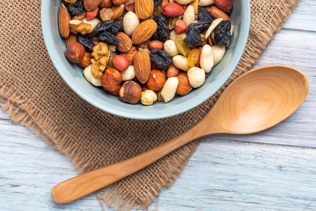 Draufsicht der mischung von nüssen und getrockneten früchten in einer schüssel auf rustikalem