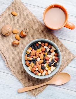 Draufsicht der mischung von nüssen und getrockneten früchten mit einer tasse tee auf sackleinen