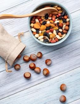 Draufsicht der mischung von nüssen und getrockneten früchten und haselnüssen, die von einem beutel auf einem holz verstreut sind