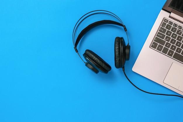 Draufsicht der mit dem laptop verbundenen kopfhörer auf blauem hintergrund. das konzept der arbeitsplatzorganisation. geräte zum aufnehmen, kommunizieren und musikhören. flach liegen.