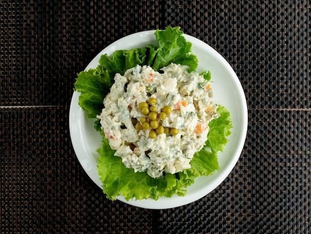 Draufsicht der mit salat garnierten olivier-salatschüssel