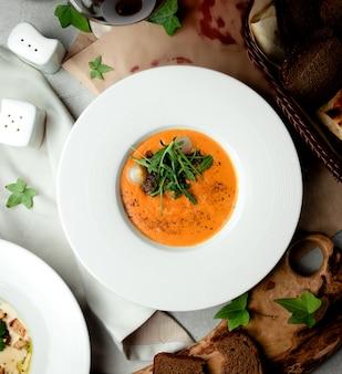 Draufsicht der mit schalotten und rucola garnierten gemüsesuppe
