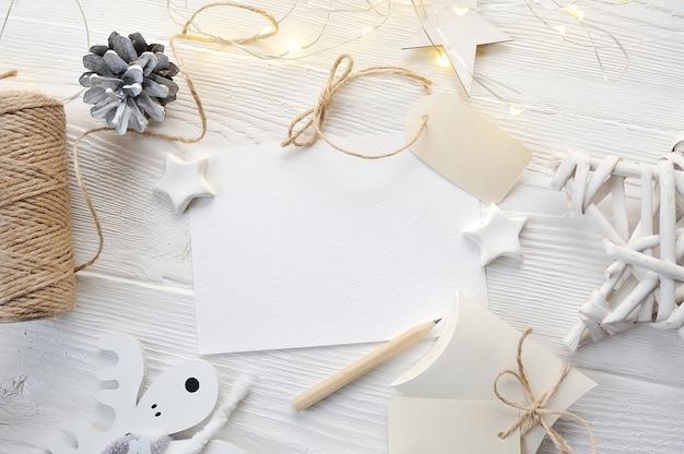 Draufsicht der modell-weihnachtsgrußkarte, flatlay auf einem weißen hölzernen hintergrund