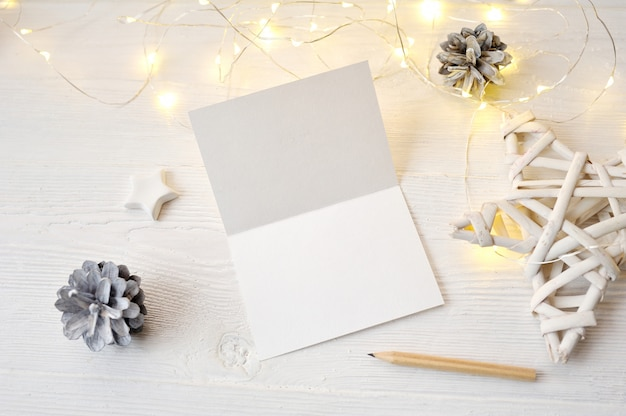 Draufsicht der modell-weihnachtsgrußkarte, flatlay auf einem weißen hölzernen