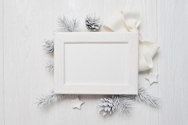 Draufsicht der modell-weihnachtsgrußkarte und weißer rahmen, flatlay