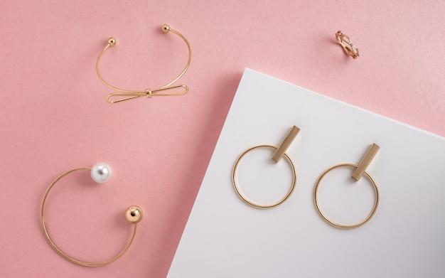 Draufsicht der modernen goldenen mädchenzubehörarmbänder und -ohrringe auf rosa und weißer oberfläche