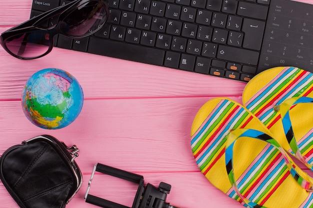 Draufsicht der modernen jungen dame im urlaub. sandalen globusbrille auf rosa hintergrund. sommerferien-accessoires der frau, die auf rosa hintergrund komponiert sind. strandmode, sommerkonzept.