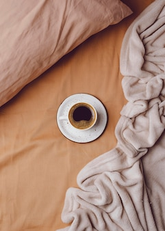 Draufsicht der morgenkaffeetasse auf bett