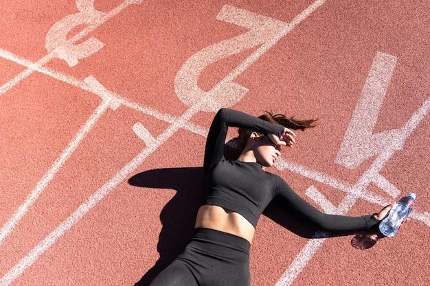 Draufsicht der müden fit frau in sportbekleidung, die nach dem training oder laufen auf einem laufbandgummistadion ruht